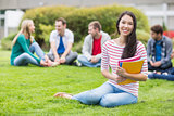Smiling college student with blurred friends sitting in the park