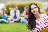 Smiling college student with blurred friends in the park