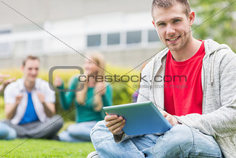 Smiling college boy holding tablet PC with students in park