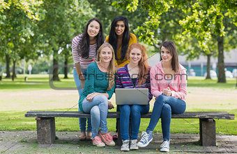 Portrait of young college girls with laptop in park