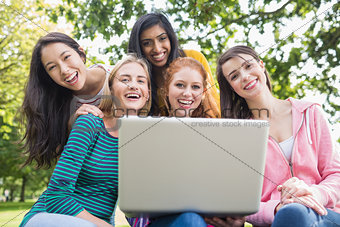 Portrait of college girls using laptop in park
