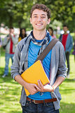 College boy holding books with blurred students in park