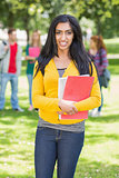 College girl holding books with blurred students in park