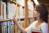 Female student selecting book in the library