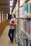Female student standing against bookshelf in the library