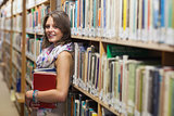 Female student leaning against bookshelf in the library