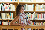 Female student with books standing in the library