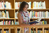 Female student reading a book in the library