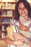 Smiling female student standing in the library