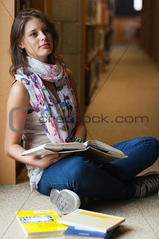 Thoughtful student sitting with books in the library