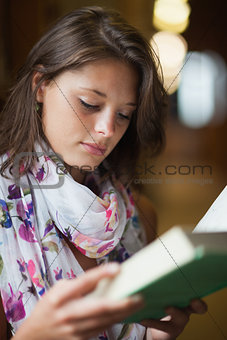 Close up of a beautiful female student reading a book