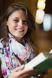 Portrait of a beautiful smiling female holding a book