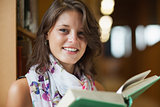Close up portrait of a beautiful smiling female holding a book