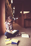 Female student reading a book in the library aisle