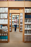 Full lenght of a female student standing in the library