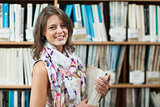 Smiling female student against bookshelf in the library
