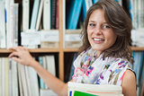 Close up portrait of a smiling female student against bookshelf in the library