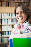 Smiling female student against bookshelf in library