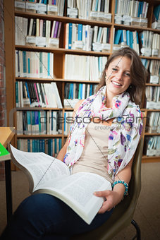 Happy female student with a book in the library