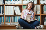 Smiling female student against bookshelf reading a book on the library floor