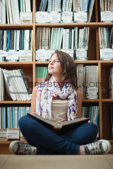 Thoughtful female student against bookshelf with a book on the library floor