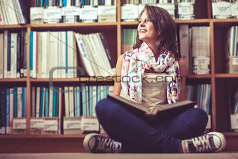 Thoughtful female student against bookshelf on the library floor