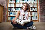 Happy female student against bookshelf with a book on the library floor