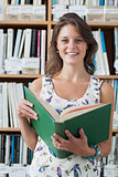 Smiling female student with a open book against bookshelf in library