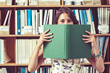 Student holding book in front of her face in library