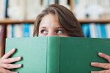 Female student holding book in front of her face in library