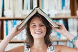 Female student holding book over her head in library