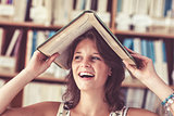 Cheerful student holding book over her head in library