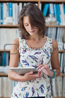 Female student against bookshelf using tablet PC in library