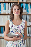 Happy female student against bookshelf holding tablet PC in library