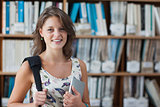Happy female student against bookshelf with tablet PC and bag in library