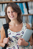 Female student against bookshelf with tablet PC and bag in library