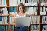 Female student against bookshelf using laptop in library