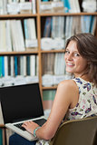 Smiling female student against bookshelf using laptop in library