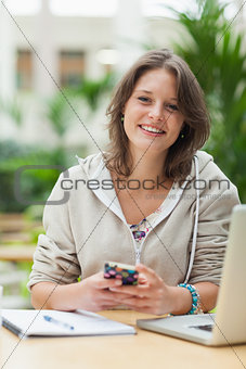 Female student with cellphone and laptop at cafeteria table