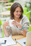 Student drinking coffee while using laptop at cafeteria table