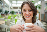 Smiling female student drinking coffee in the cafeteria
