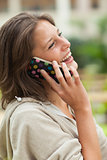 Side view of a cheerful woman using mobile phone