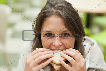 Close up portrait of a female student eating sandwich