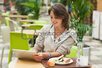 Woman using tablet PC in the cafeteria