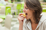 Close up side view of a young woman eating apple