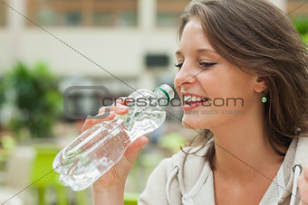 Close up side view of a young woman drinking water