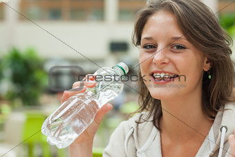 Close up portrait of a young woman drinking water
