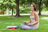 Female student sitting with books at the park