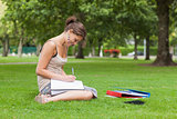 Female student doing homework at the park