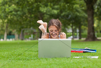 Female student with laptop and books at the park